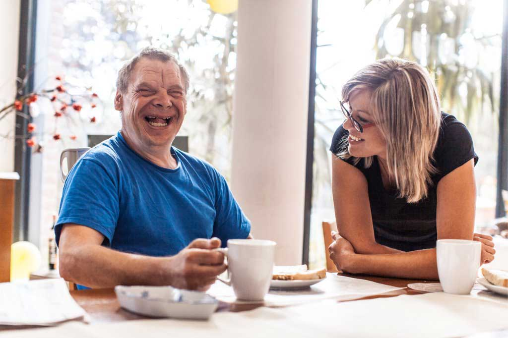 Adult man with down syndrome and a caregiver