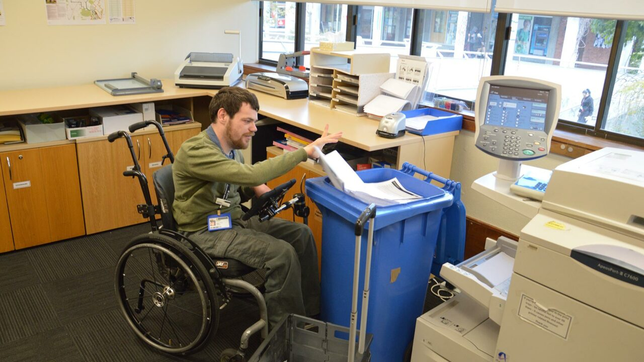 Man in a wheelchair working in a office