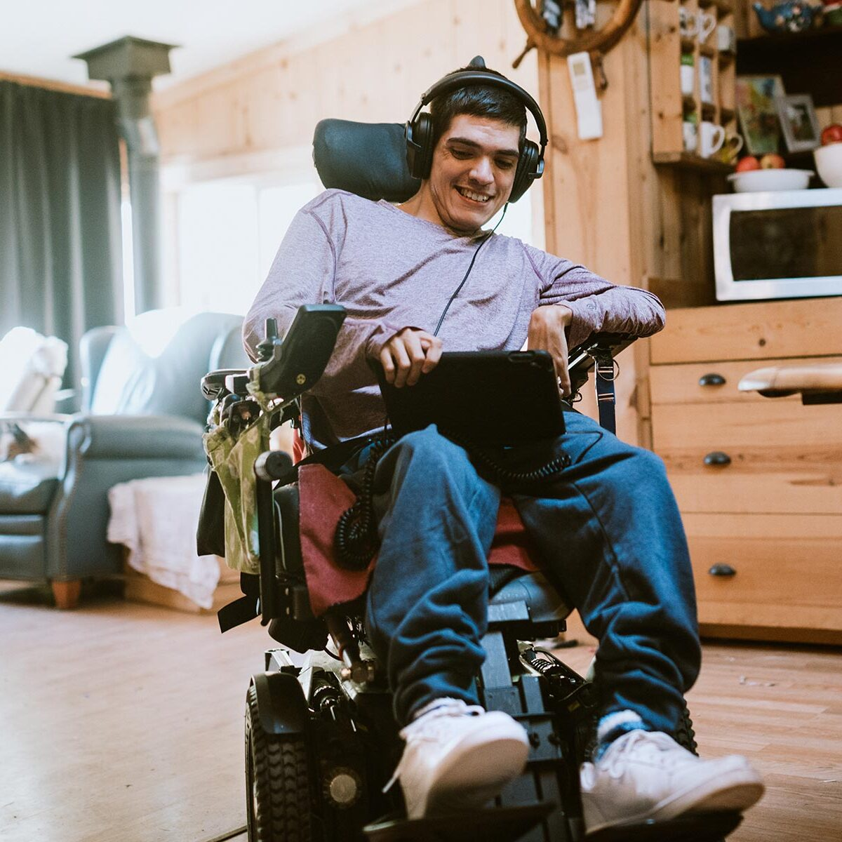Smiling man at home in an electric wheelchair