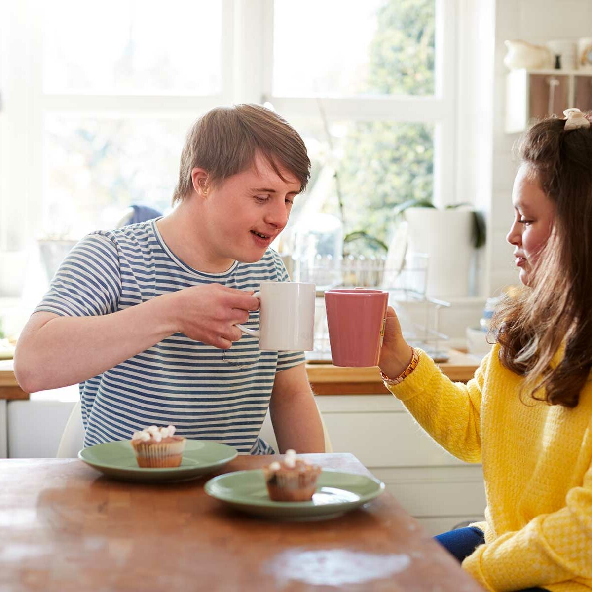 A young man with Downs syndrome drinking tea with a friend